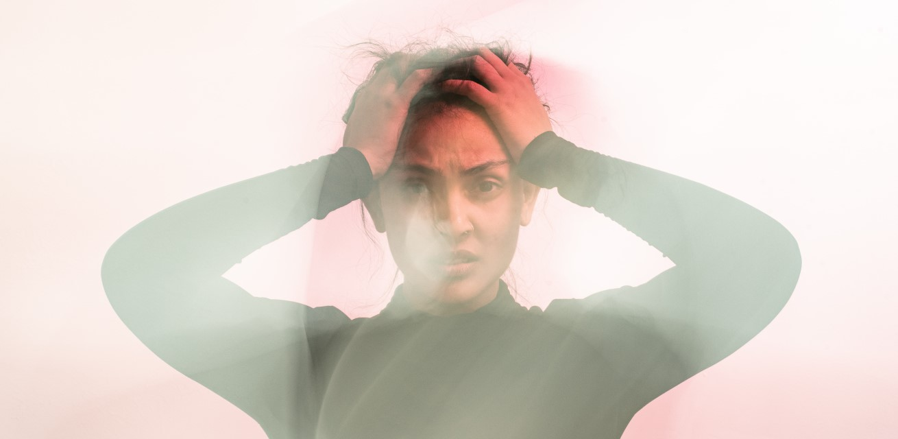 Vrouw houdt wanhopig handen tegen het hoofd.