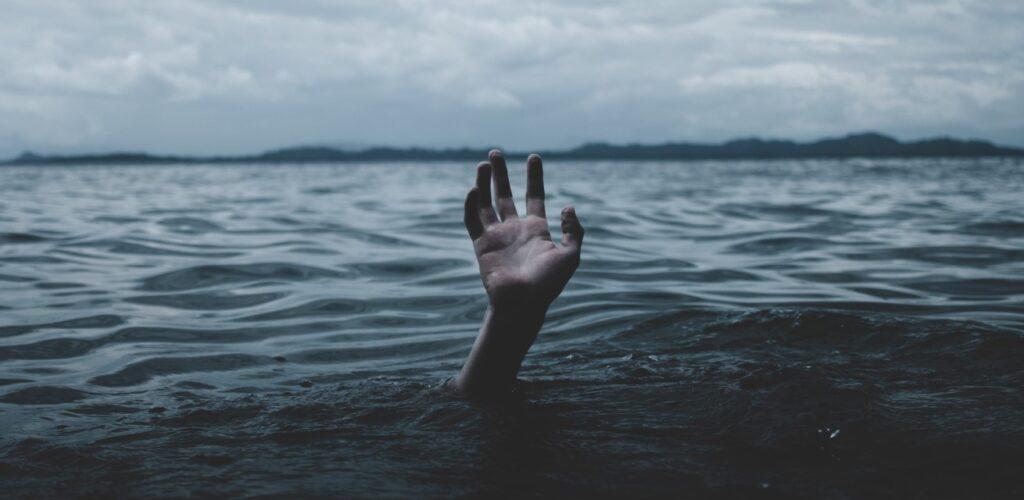 Hand steekt uit boven het water van een meer.