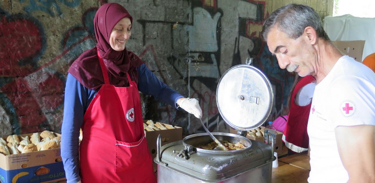 Bosnië-en-Herzegovina-Bihac.-17-Juli-2018.-Rode-Kruis-vrijwilligers-geven-voedsel-aan-migranten-bij-grens-met-Kroatië.