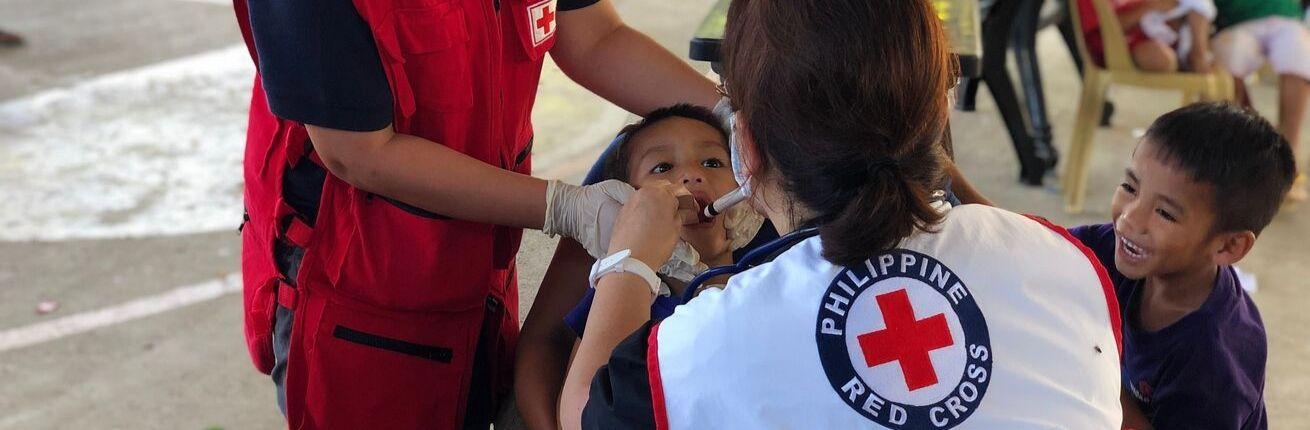 Kind-wordt-gevacinneerd-door-Rode-Kruis-dokter-op-de-Filippijnen