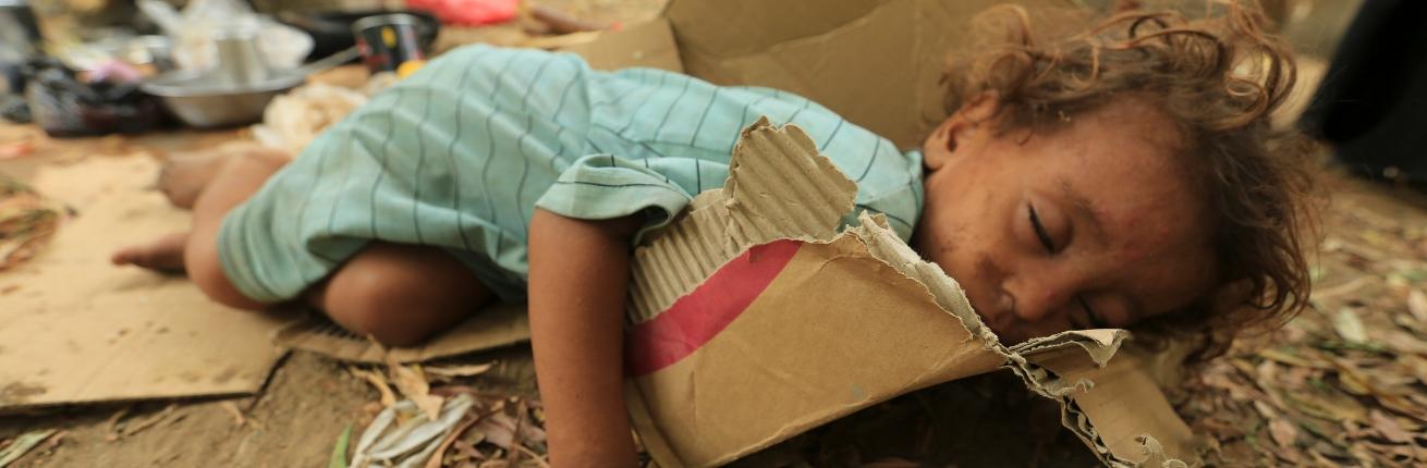 Meisje slaapt op karton in Jemen