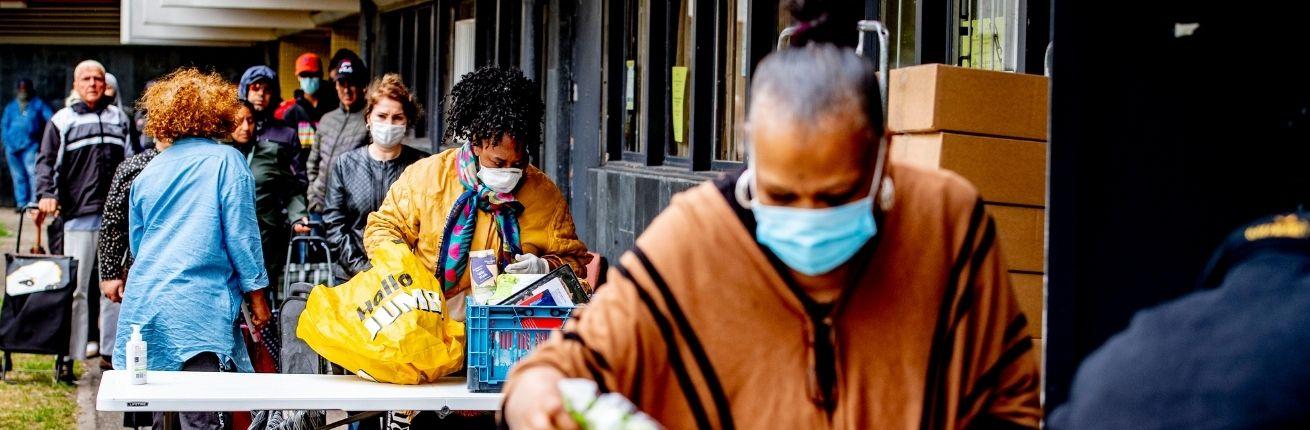 Mensen in voedselnood krijgen voedselpakketten van het Rode Kruis