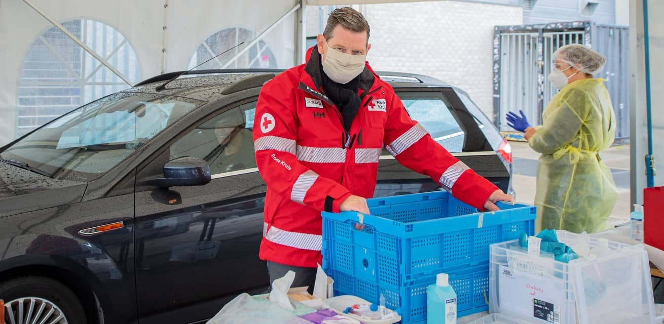 Rode Kruis vrijwilliger helpt in corona teststraat