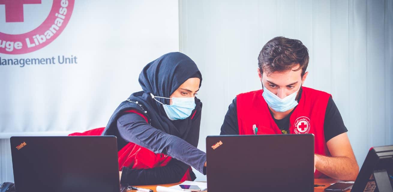 Doe een donatie aan het Rode Kruis - Doneren - Rode Kruis hulpverleners achter laptop