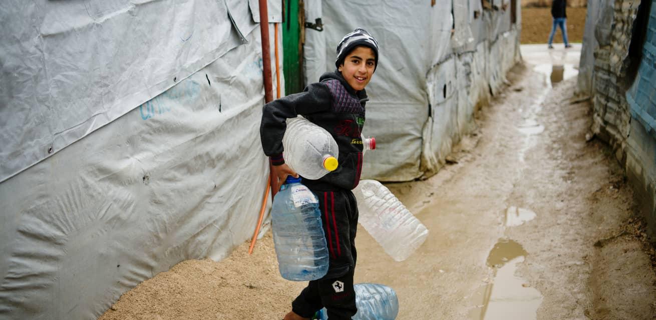 kind haalt water in syrisch vluchtelingenkamp