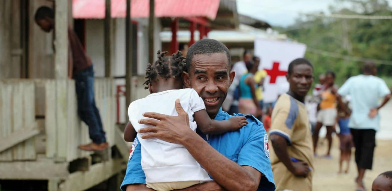 Rode-Kruis-vrijwilliger-met-kindje-op-de-arm