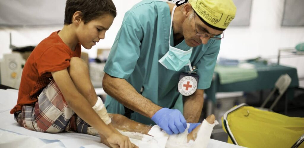 chirurg helpt jongen in kliniek kamp Al Hol Syrië Rode Kruis