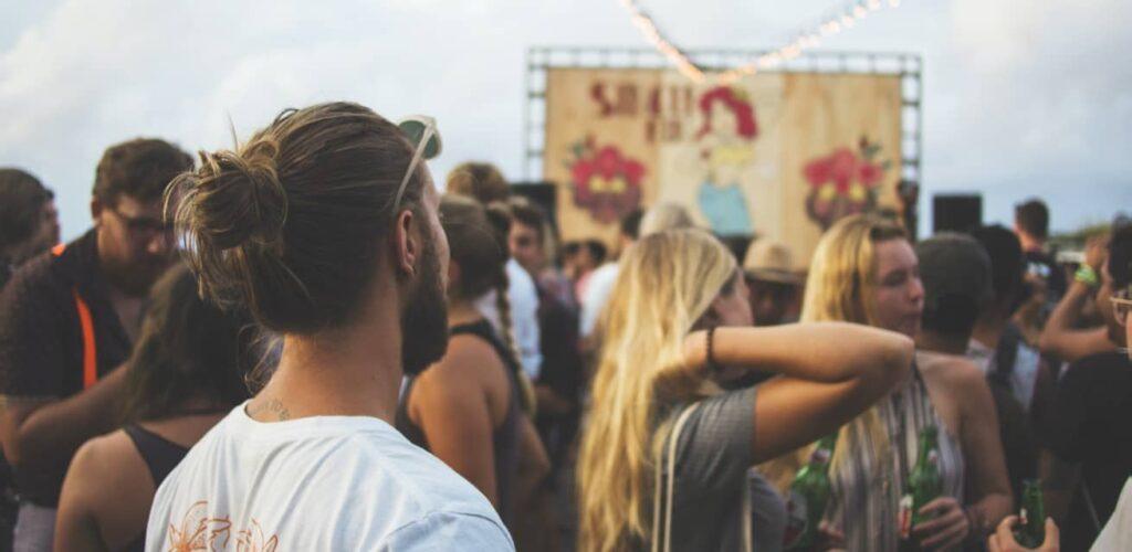 Man staat op een feestje met zijn rug naar de camera en kijkt naar een groepje mensen dat praat en een drankje drinkt.