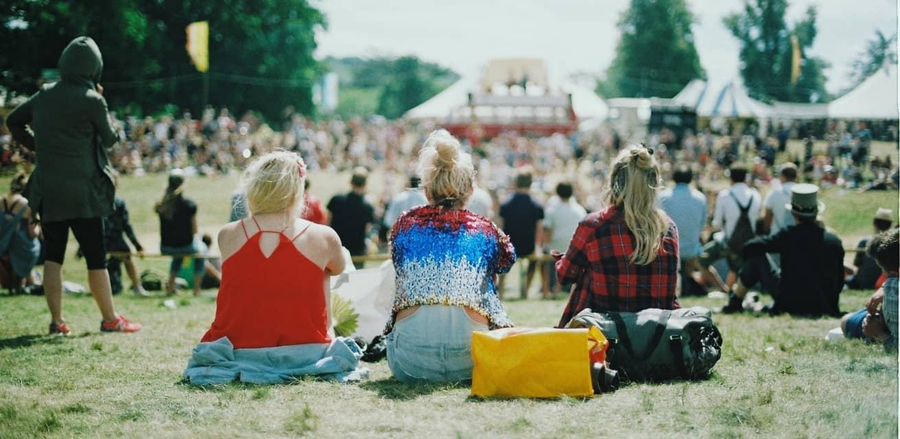 Drie meisjes zitten met hun rug naar de camera op een grasveld tijdens een festival.
