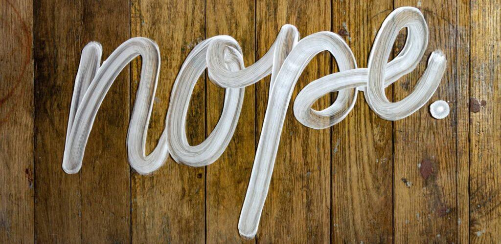 Houten achtergrond met witte letters erop die 'nope' spellen