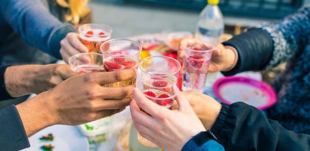 Mensen proosten met glazen met een zomers drankje.