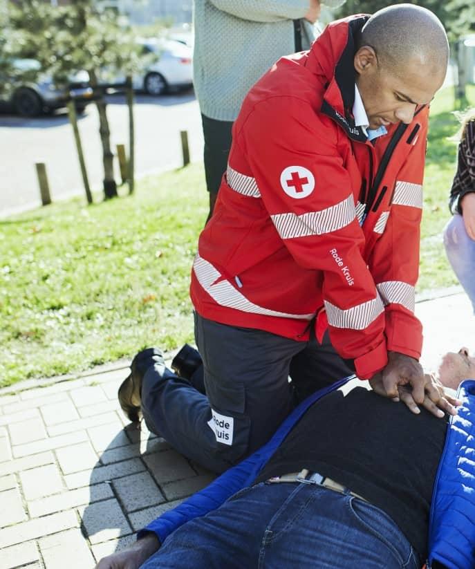 rode kruis vrijwilliger helpt bij een ehbo situatie door te reanimeren