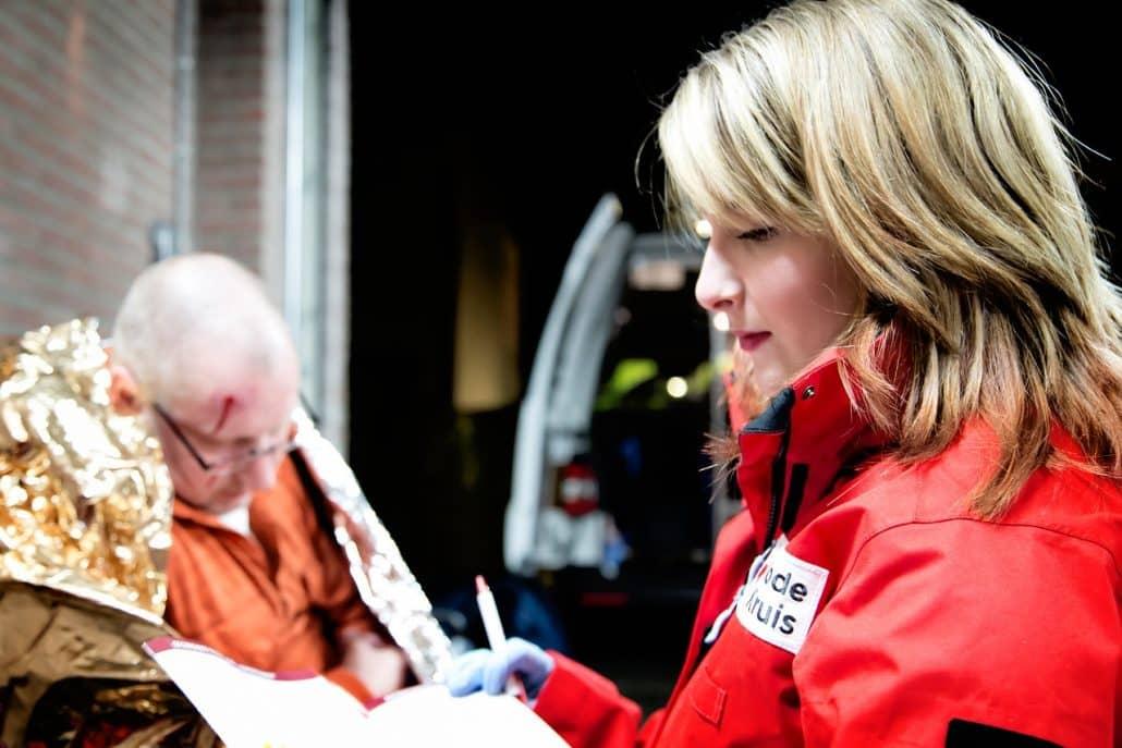 rode kruis vrijwilliger helpt bij een ehbo situatie