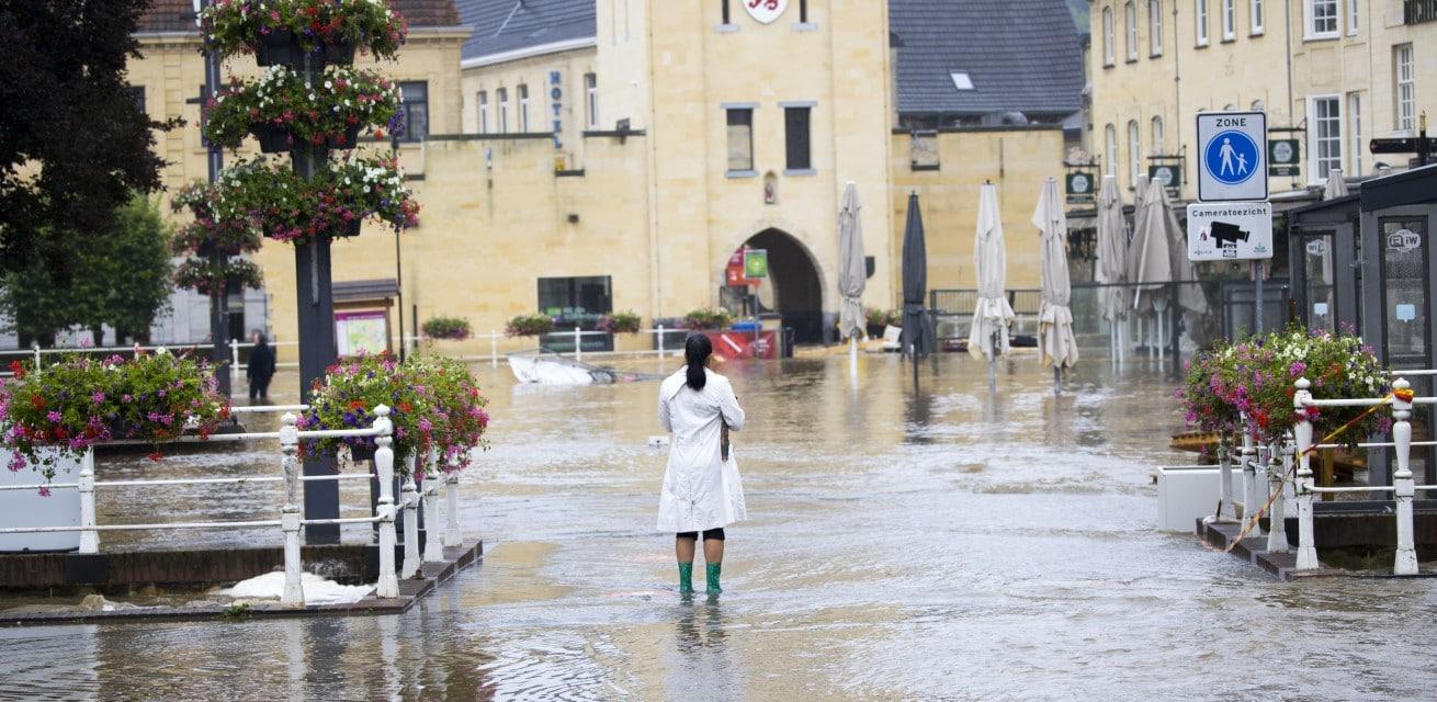 vrouw middenin overstromingen in limburg Rode Kruis