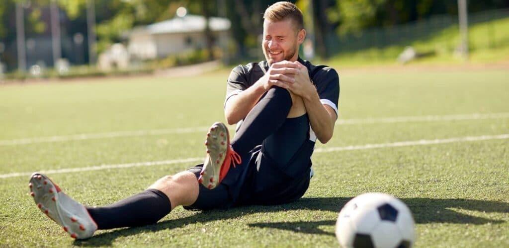 Geblesseerde voetbalspeler met kramp heeft eerste hulp nodig