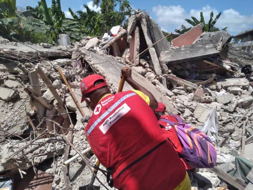 Hulpverleners zoeken naar mensen onder het puin na de aardbeving op Haïti Rode Kruis