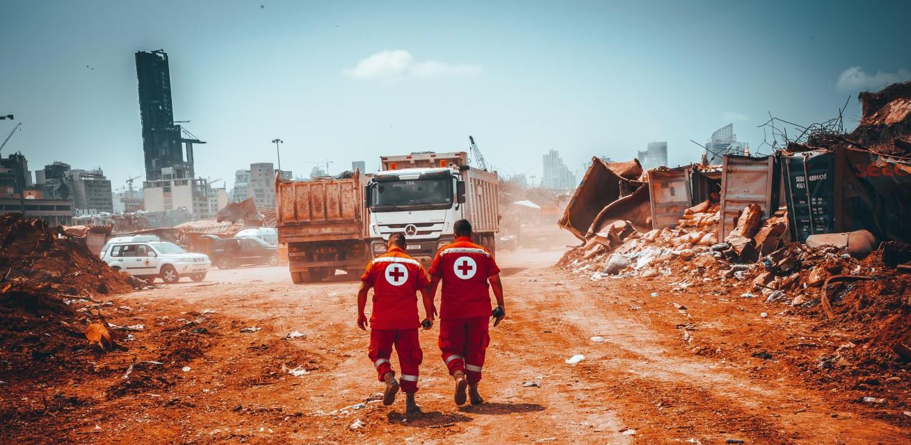 hulpverleners van het Rode Kruis lopen door het puin na explosie Beiroet
