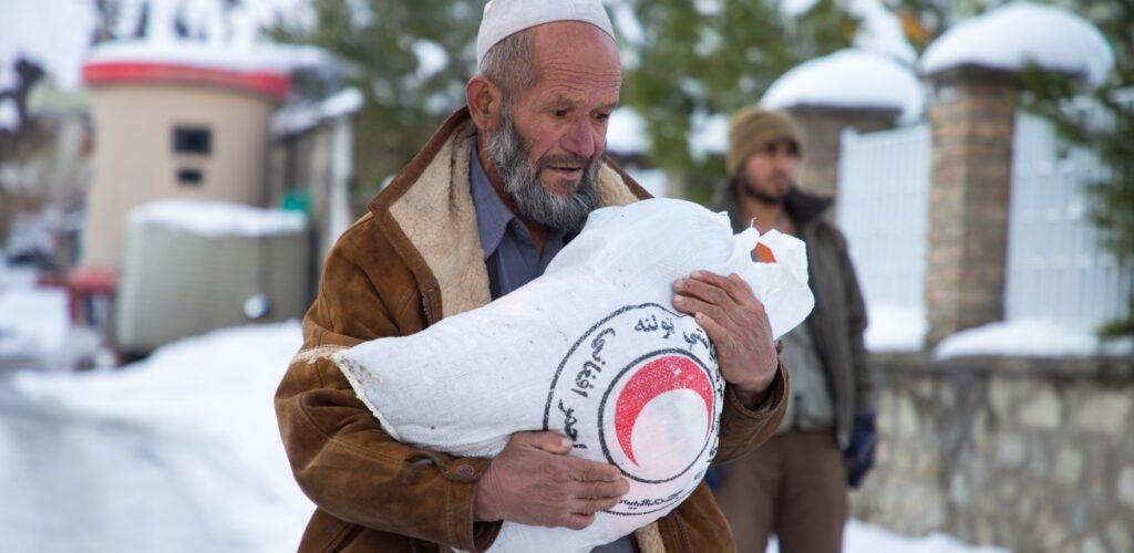 man met hulpgoederen in winter in Afghanistan Rode Kruis