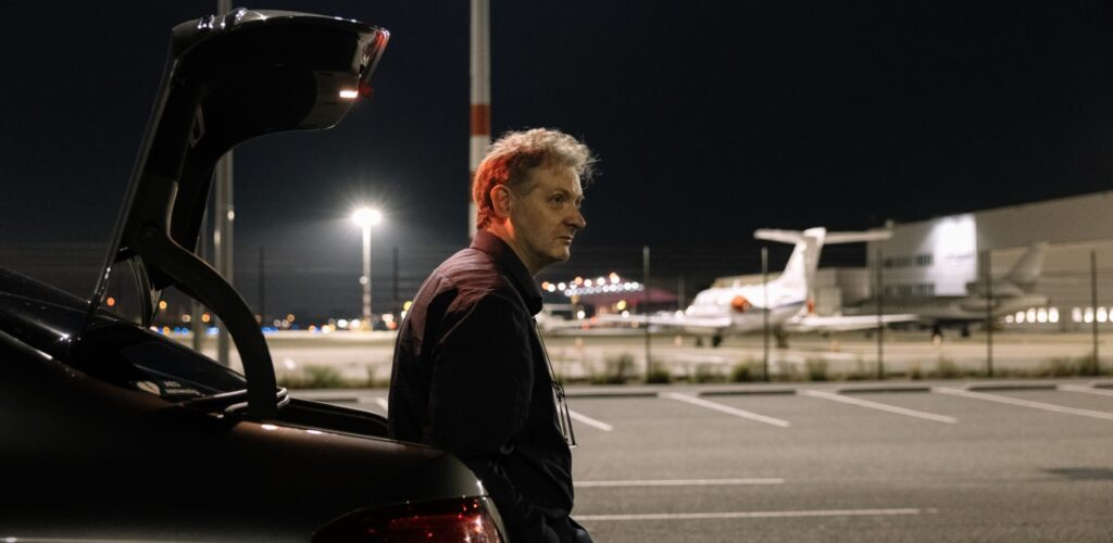 taxichauffeur Marko wacht op de luchthaven voor een klant Rode Kruis