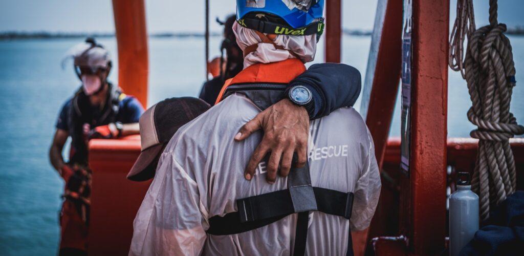 vluchteling op de middellandse zee omhelst reddingswerker Rode Kruis
